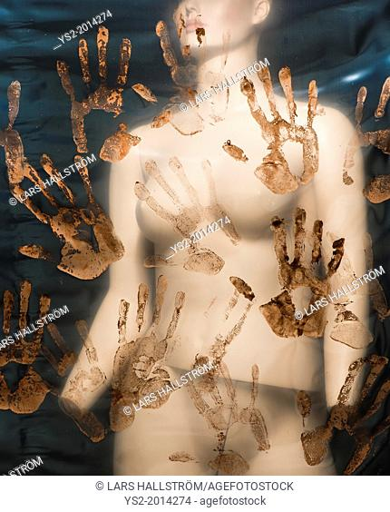Female mannequin behind plastic sheet that is covered with red handprints. Conceptual image of abuse and sexual violence against women