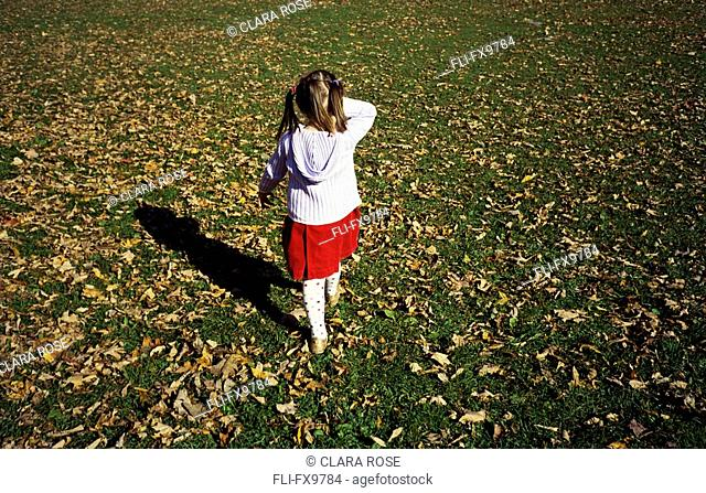 Little girl walking on the grass covered with falling leaves, Montreal, Quebec