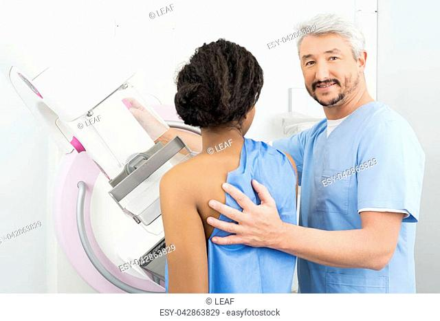 Portrait of mature doctor assisting patient undergoing mammogram X-ray test in hospital