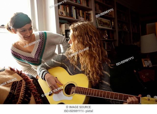 Teenage girls, one playing guitar