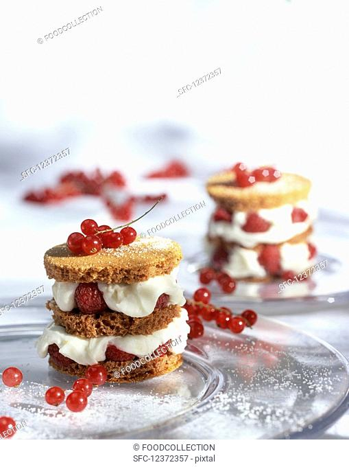 Raspberry layered tarts with whipped cream and red currants