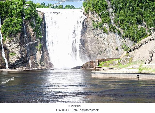 Fishermen in the river are dwarfed by the spectacular height of Montmorency Falls