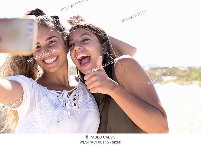 Girlfriends having fun on the beach, taking smartphone selfies