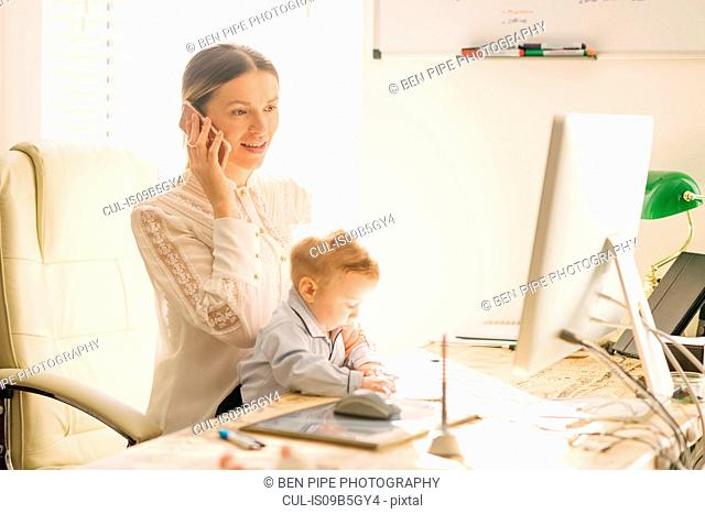 Mother working and caring for baby at home
