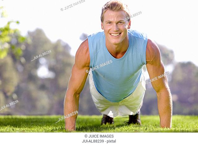 Man doing push-ups in grass