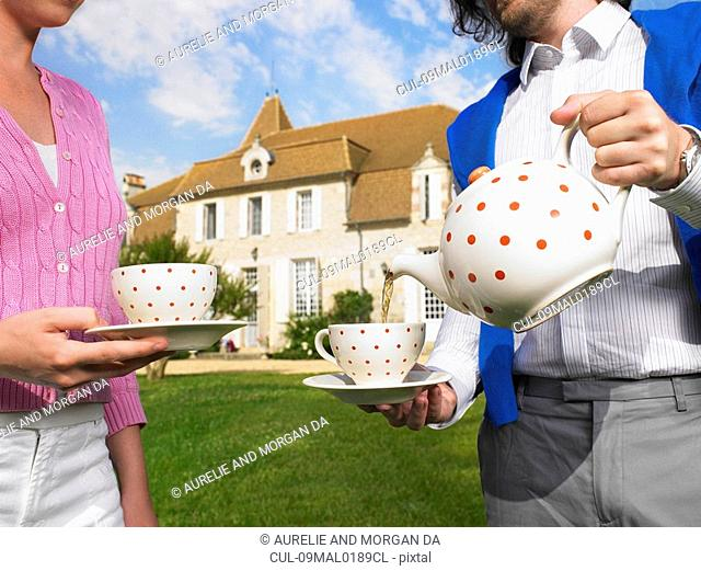 Drinking tea in front of country home