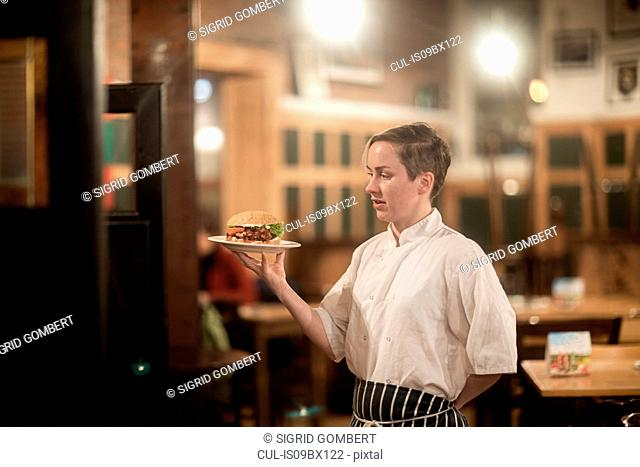 Waitress serving plate of burger in gastro pub