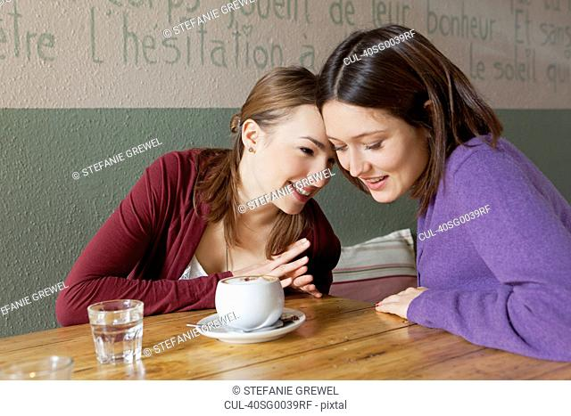 Women whispering to each other in cafe