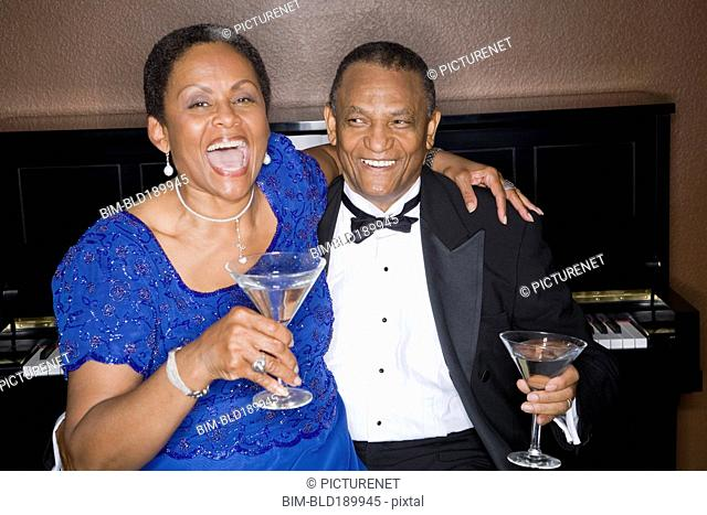 Well dressed african couple drinking cocktails in front of piano