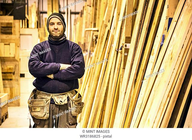 Bearded man wearing beanie and tool belt standing with his arms crossed next to a stack of wooden planks in a warehouse, looking at camera