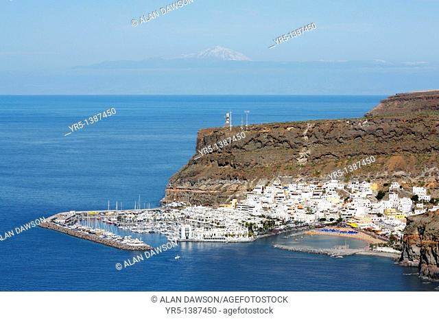 Aerial view of Puerto de Mogan on Gran Canaria with snow covered El Teide, Spain's highest mountain, on Tenerife in distance  Canary Islands, Spain