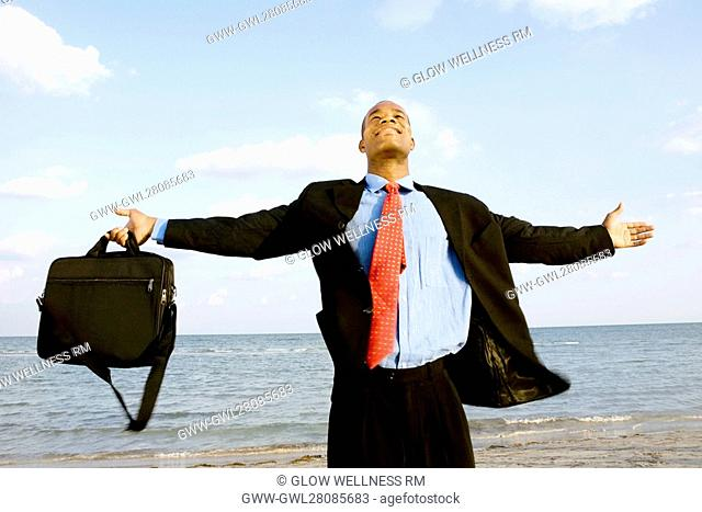 Businessman standing on the beach with his arm outstretched