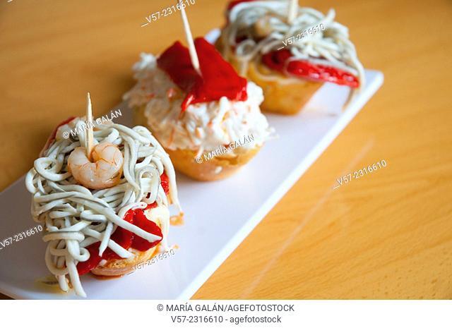 Spanish tapa: prawns, gulas and surimi salad with red pepper. Close view
