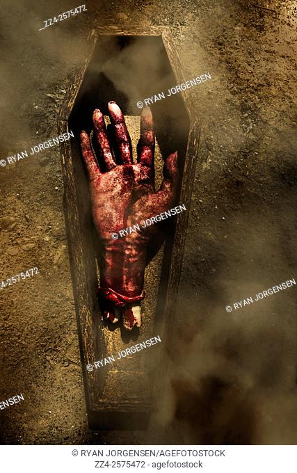 Severed hand lying dead in a open coffin on dirt cemetery path. Goodbyes and farewells