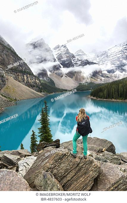 Young woman standing in front of a lake looking into mountain scenery, clouds hanging between mountain peaks, reflection in turquoise lake, Moraine Lake