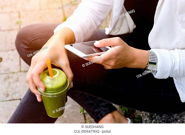 Cropped shot of young woman sitting with smootie drink using smartphone