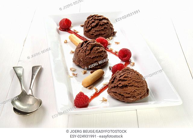 chocolate ice cream with fruit sauce, raspberries and chocolate curls on a white plate