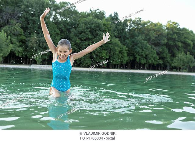 Cheerful girl with arms raised enjoying in swimming pool against trees