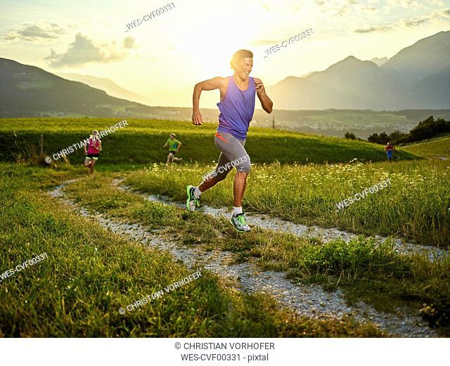 Athletes running on field path at sunset