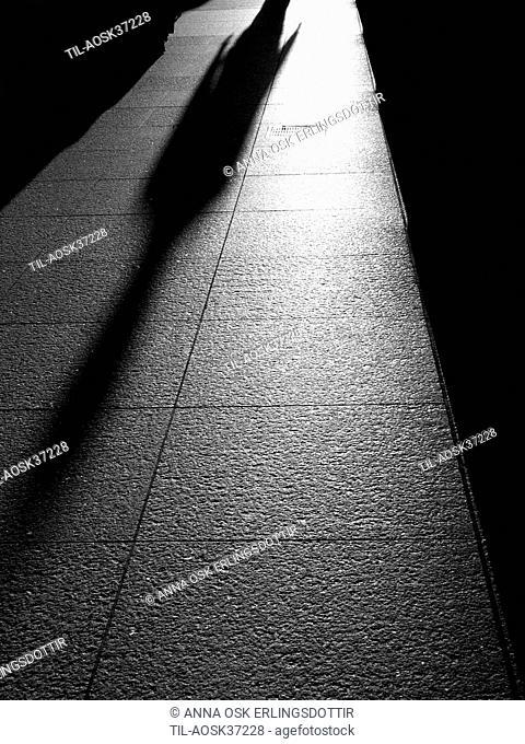 Shadow of lonely figure walking along street