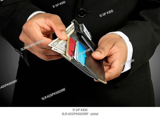 Businessman counting money in wallet
