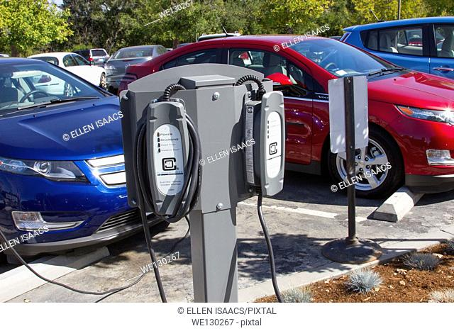 EV charging stations with electric cars plugged and charging in at a company parking lot