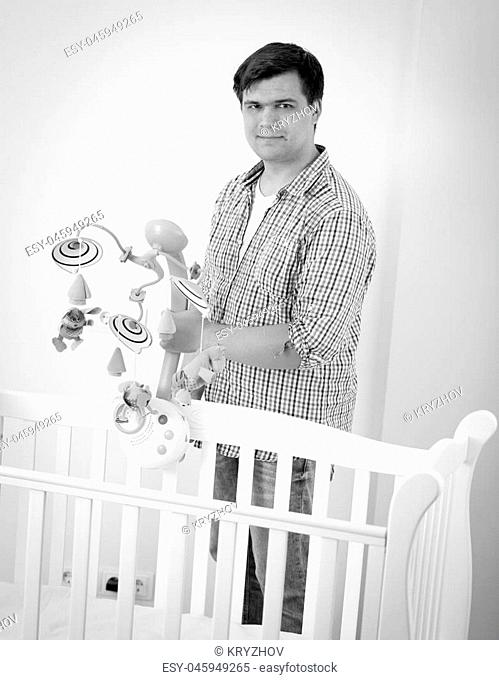 Black and white image of young caring father assembling baby's cot and putting toy carousel in it