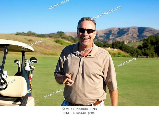 Caucasian man with cigar playing golf on golf course