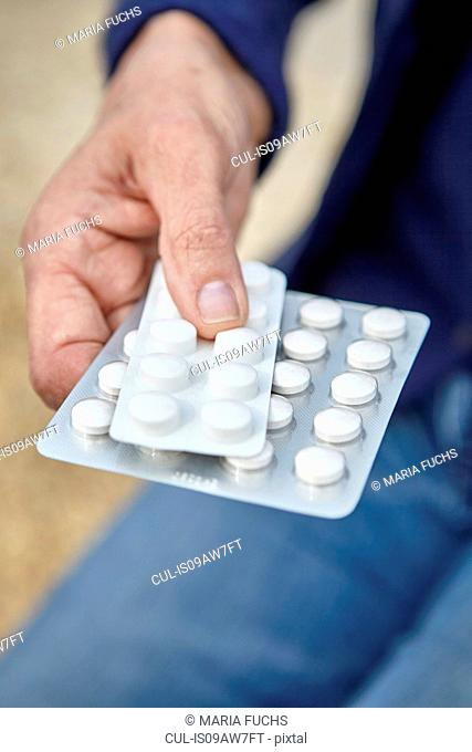 Womans hand holding blister packs of pills