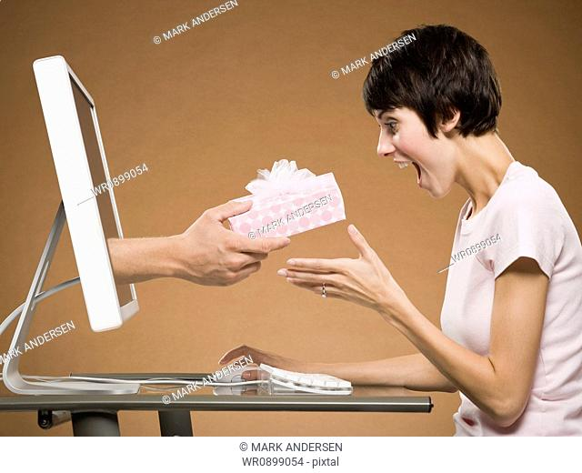 Woman sitting at computer with hand emerging from monitor holding gift box