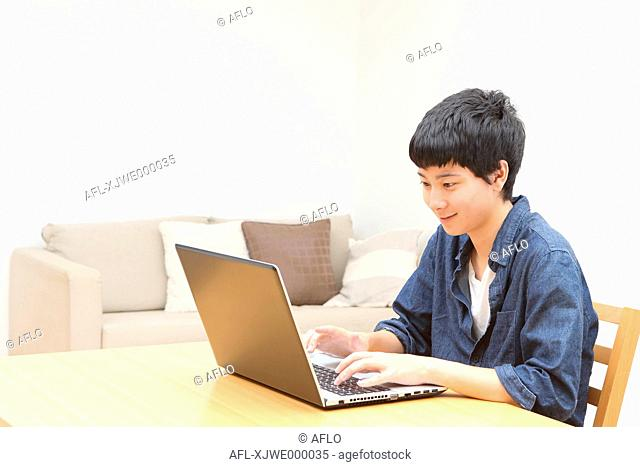 Young Japanese man working with notebook