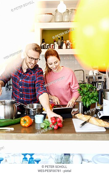 Happy young couple with tablet cooking together in kitchen