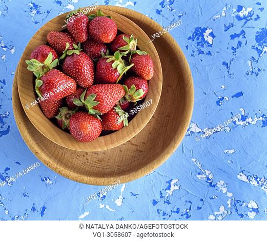 fresh ripe red strawberries in a brown wooden round plate on a blue textural background, top view, copy space