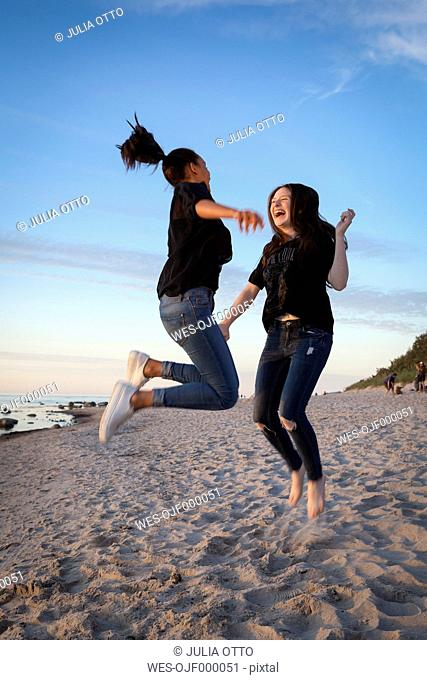 Germany, Ruegen, Two young female friends jumping at the beach