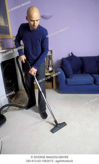 Man hoovering carpet in his living room at home UK