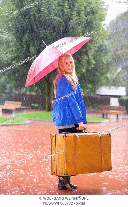 Austria, Thalgau, teenage girl with red umbrella standing in the rain with suitcase