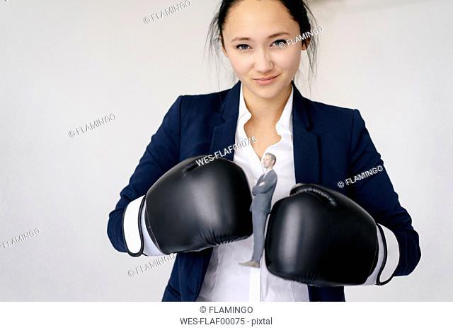 Businesswoman holding businessman figurine between boxing gloves