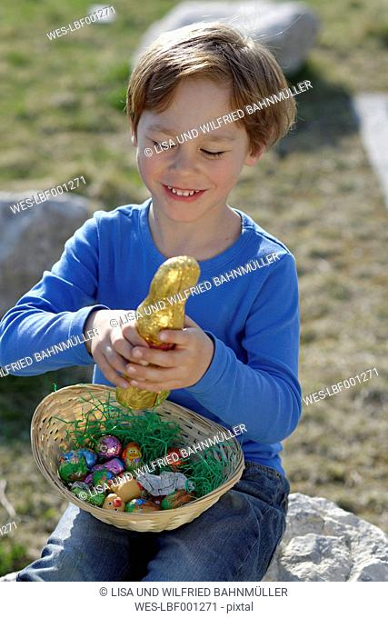 Portrait of smiling little boy with Easter nest and Easter bunny