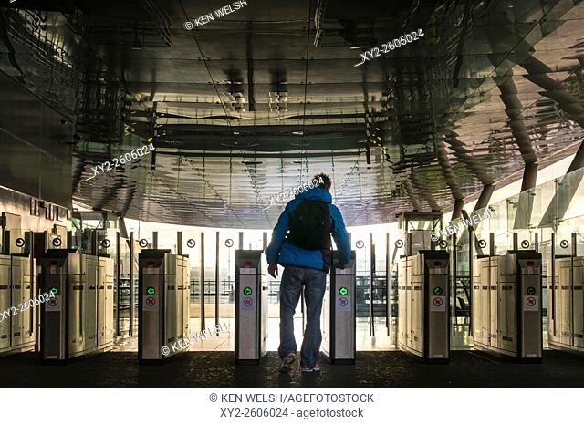 Passenger inserting ticket at automatic gate at train station