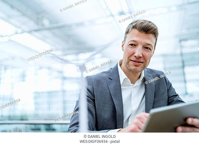 Businessman with wind turbine model and tablet
