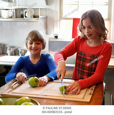 Two young girls in kitchen, cutting apples on chopping board