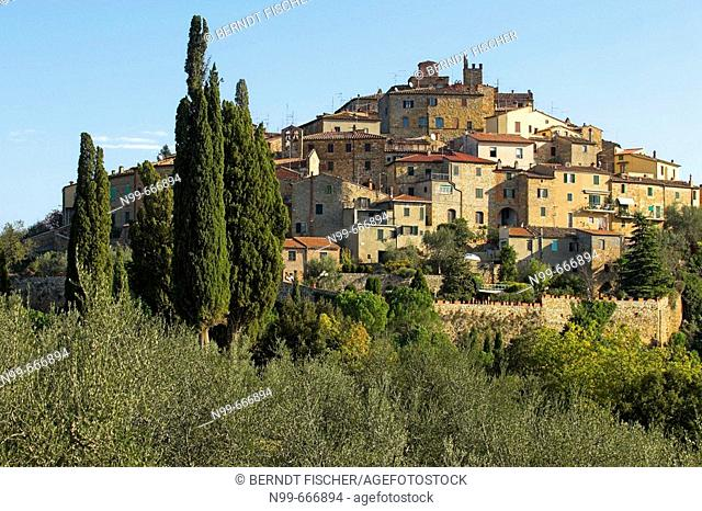 Petroio, Tuscan village on top of a hill, near Pienza, cypresses (Cupressus sempervirens)  and olive trees, colours of autumn, Tuscany, Italy