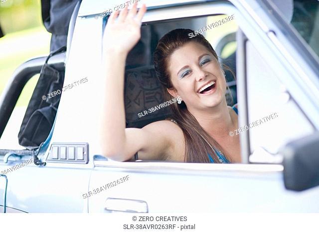 Teenage girl waving from car