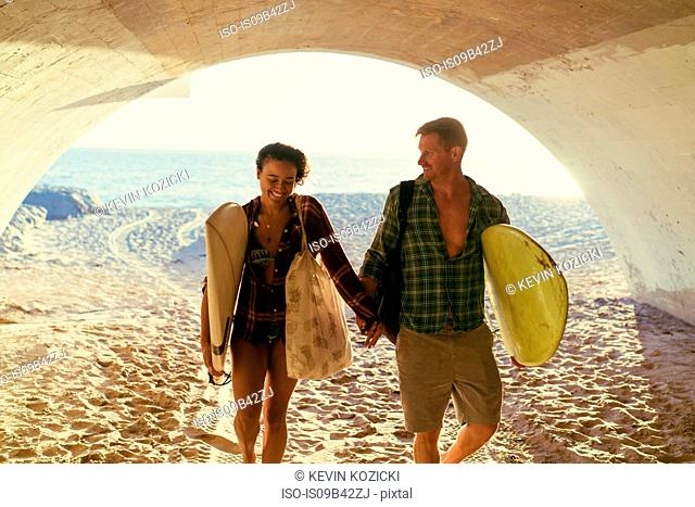 Surfing couple walking in underpass at Newport Beach, California, USA