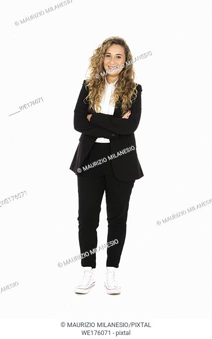 Smiling girl with curly blonde hair, she is standing with her arms crossed, wearing a black suit and white shirt and sneakers