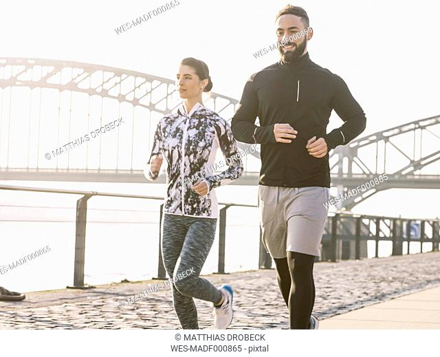 Germany, Cologne, Young couple jogging