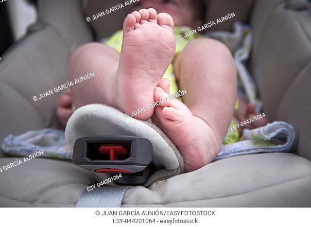 Newborn baby feet over at i-size baby car seat. Low angle shot