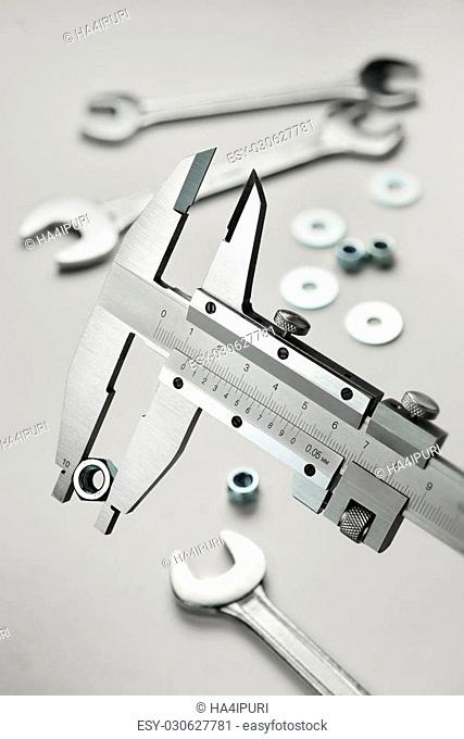 Vernier caliper measuring steel nut with different metal wrenches on background