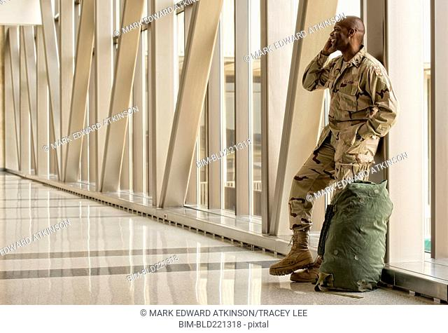 African American soldier talking on cell phone in airport