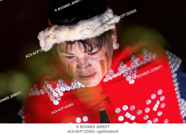 Soft light illuminates the painted face of a first nations woman and her ceremonial regalia, Comox, The Comox Valley, Vancouver Island, British Columbia, Canada